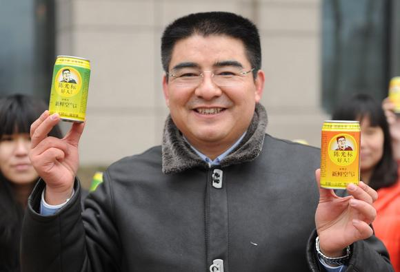 Chen Guangbiao holding cans of air
